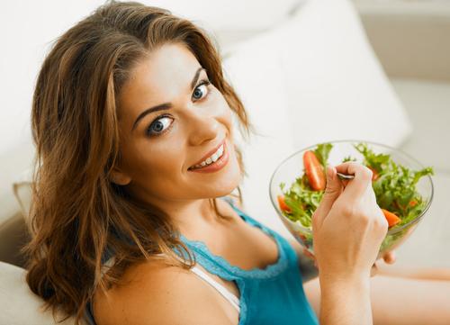 Mujer comiendo alimentos saludables ensalada